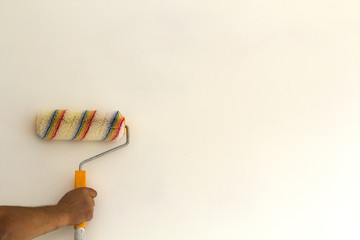 Worker hand with paint roller brush near wall in renovated room interior isolated on white background. Renovation and DIY concept.