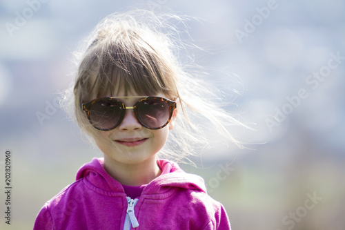 4068794f0c8f Portrait of cute pretty little blond preschool girl in pink sweater and  dark sunglasses smiling happily in camera with funny child smile against  blurred ...