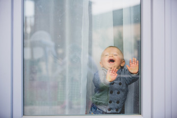 Cute toddler boy, staying at home behind the glass doors, watching outside