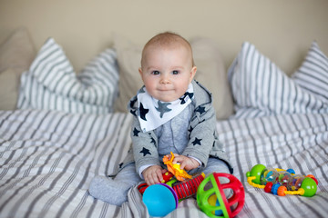 Cute little baby boy, playing at home in bed with lots of colorful toys