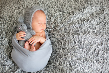 Sleeping newborn baby boy, hugging little knitted toy