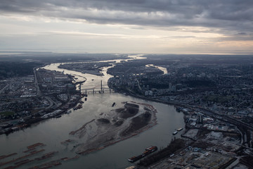 Aerial view of Fraser River during a cloudy sunset. Taken in Greater Vancouver, British Columbia, Canada.