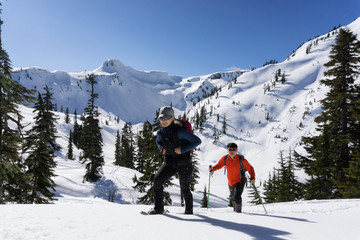 Adventurous man and woman are snowshoeing in the snow. Taken in Artist Point, Northeast of Seattle, Washington, United States of America.