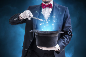 Magician or illusionist is showing magic trick. Blue stage light in background. Fotoväggar