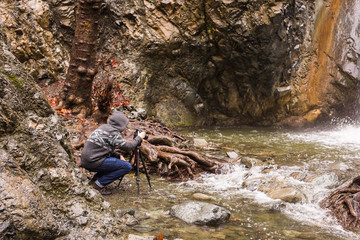 Young photographer with backpack making photos of waterfall and rocks with the camera. Mediterranean sea