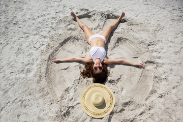 High angle view of woman making sand angel at beach