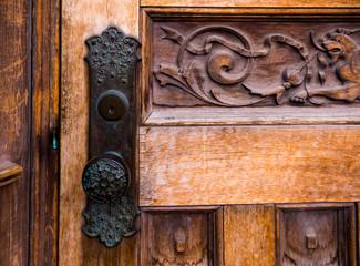 horizontal image of old 1900s building wood door with black door knob and carved details