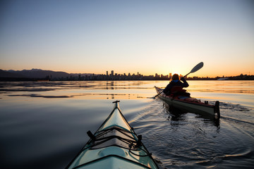 Adventurous girl on a sea kayak is kayaking during a vibrant sunny sunrise. Taken in Downtown Vancouver, British Columbia, Canada.