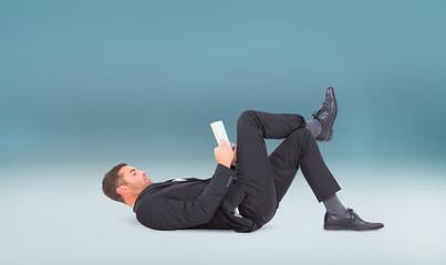 Businessman lying on the floor reading book  against blue vignette background