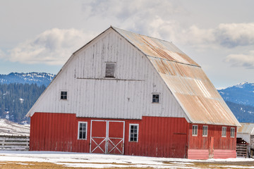 Unique red and white barn located on an Idaho farm with snow in the mountains