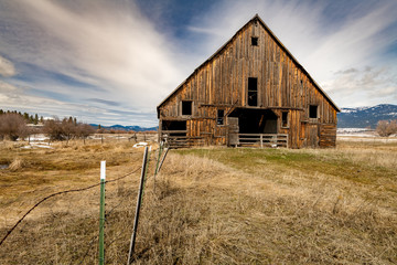 Farmers barn with barbed wire fence and clouds streaks in the sky