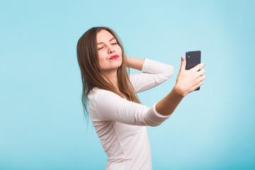 Joyful young women making selfie by her smart phone on blue background