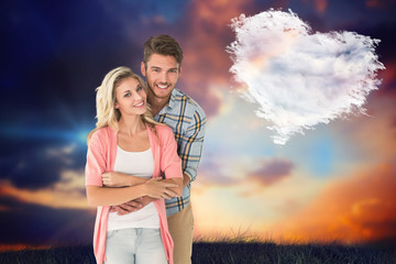 Attractive young couple smiling together against cloud heart