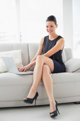 Portrait of a beautiful well dressed woman using laptop on sofa