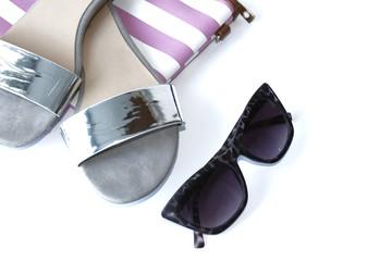 Sandalias plateadas de verano, gafas de sol y cartera de mano a rayas rosa y blana. FONDO BLANCO