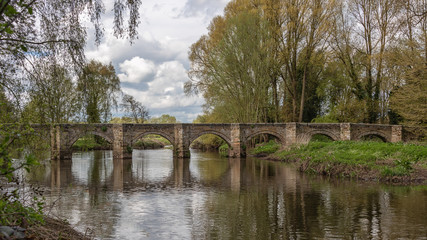a landscape photograph of a long packhorse bridge made of stone and spanning the river trent