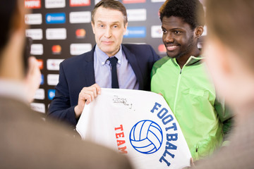 Portrait of smiling African-American sportsman taking selfie with fan posing for photo with his coach and holding signed t-shirt