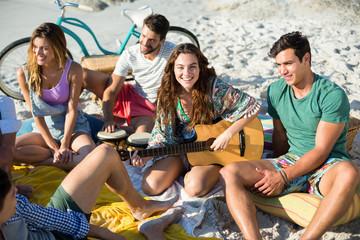 Friends enjoying while sitting at beach