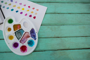 Colorful palette and paper on wooden surface