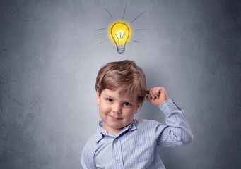 Adorable little kid mull over in front of a grey wall with idea symbol above his head