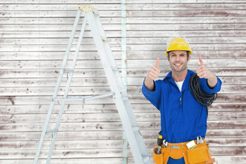 Happy electrician gesturing thumbs up by ladder against digitally generated grey wooden planks