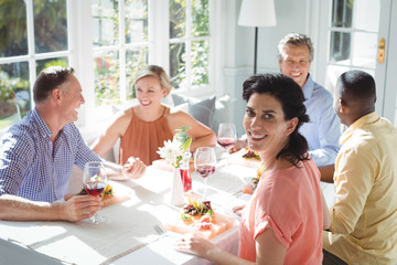 Portrait of smiling woman having meal with friends