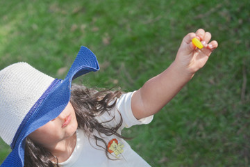 Little latin girl wearing big hat shows little yellow candy.