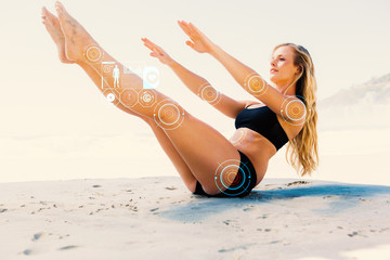 Fit blonde in core balance pilates pose on the beach against fitness interface