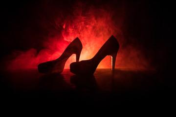 Black suede high heel women shoes on dark toned foggy background. Close up. Women power or women domination concept. Selective focus. Slider shot