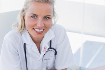 Portrait of a pretty nurse against breast cancer awareness ribbon