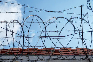 Protection Fence with Sharp Barbed Wire in the Blue Sky Background.