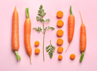 Flat lay composition with fresh carrots on color background