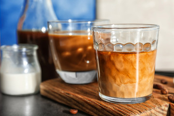 Glasses with cold brew coffee and milk on wooden board
