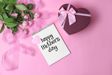 "Notebook with phrase ""HAPPY MOTHER'S DAY"", flowers and gift box on color background"