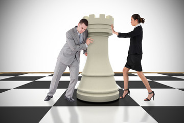 Composite image of business people pushing chess piece against white background with vignette