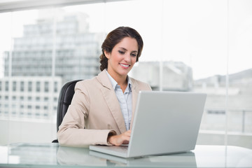 Happy businesswoman typing on laptop at her desk