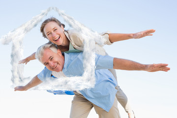 Happy casual couple having fun against house outline in clouds