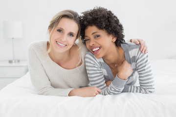Two smiling young female friends lying in bed