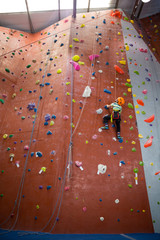 Boy practicing rock climbing in fitness studio