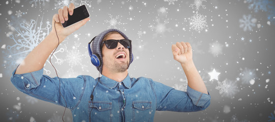 Hipster wearing sunglasses enjoying music against snowflake pattern