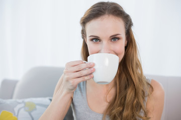 Cheerful young woman sitting on sofa holding cup