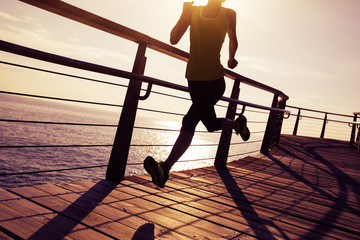 sporty female runner running on seaside boardwalk during sunrise