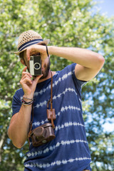 Handsome hipster using vintage camera