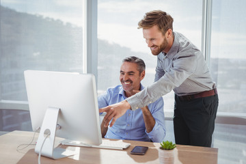 Smiling executives discussing over personal computer at desk