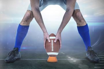 American football player placing ball between legs against american football arena