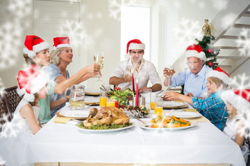Composite image of Family toasting wine while having Christmas meal against snowflakes