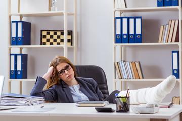 Busiesswoman employee with broken leg in office