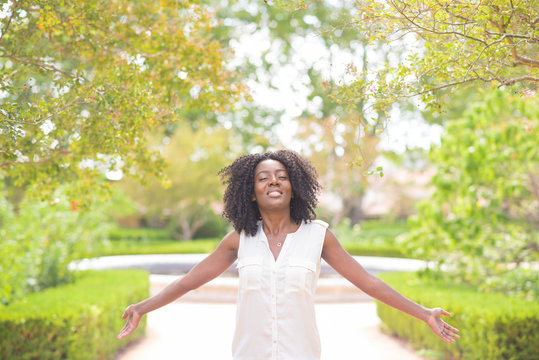 Smiling pretty black woman spreading hands in park with summer plants in background. Harmony concept. Front view.