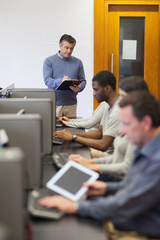 Teacher writing on clipboard in computer room