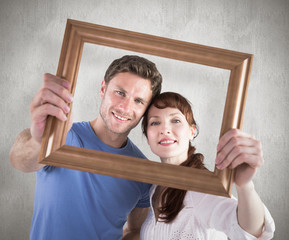 Couple holding frame ahead of them against weathered surface